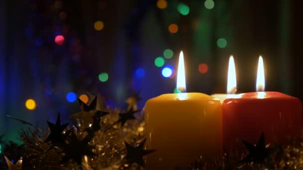 Drei Neujahrskerzen und Weihnachtsdekorationen. Verschwommener Hintergrund mit farbigen Lichtern. Verlassen Sie die Zone der Nicht-Schärfe