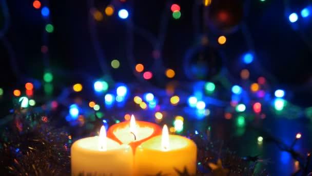 Tři nový rok svíčky close-up a nový rok girlandy. Rozmazané pozadí s barevnými světly.