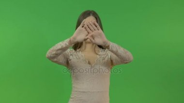 Beautiful young girl doing hand gestures on a green screen background.