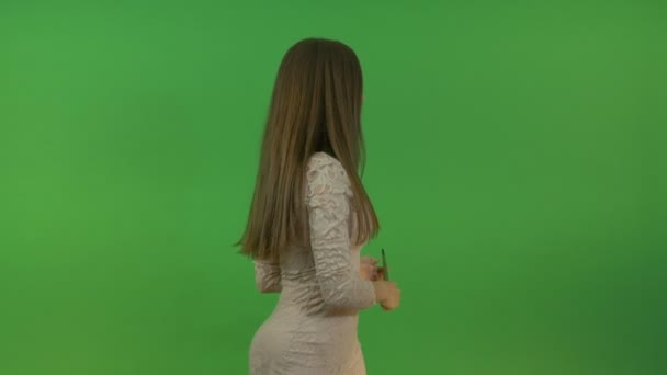 Mladá atraktivní dívka dělá gesta ukazatel. Na zeleném pozadí. Ona ukazuje na objekty za jejími zády