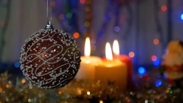 Una grande sfera rossa. Decorazioni di Natale e Capodanno. Candele accese. Lampeggiante ghirlande. Priorità bassa vaga