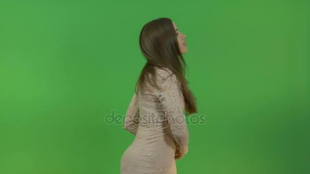 Krásná mladá dívka s dlouhými vlasy klade otázku a odkazuje na tři objekty za jejími zády. Na zelené obrazovce