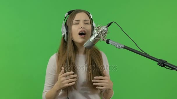 Photo A young girl is singing into a studio microphone. close-up. On a green background.