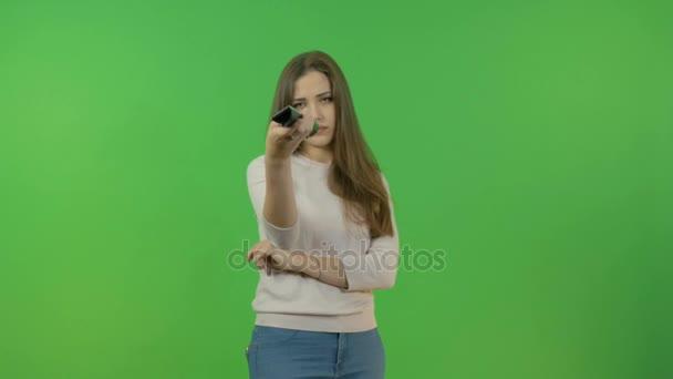 Mladá dívka přepíná kanály na dálkové ovládání televizoru. Smutné, špatné zprávy. Na zelené obrazovce.