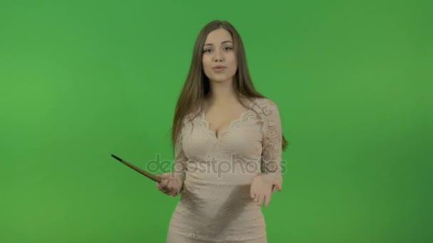 Mladá dívka v béžových šatech klade otázku a odkazuje na objekt za jejími zády. Na zelené obrazovce