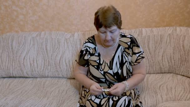 eine ältere Frau nimmt Medikamente, sitzt zu Hause auf der Couch.