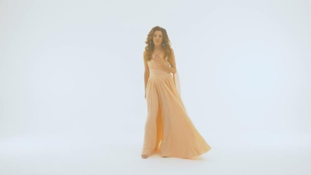 Lassú mozgás az énekes egy hosszú gyönyörű ruha énekel, a háttérben a fehér falra. Ő terjed a kezét, más-más irányba.