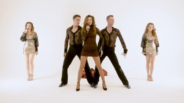 Skupina profesionálních herců, tanec na bílém pozadí. Zpěvák dívka v černých šatech. Dva mladí muži v černých oblecích tanec. Dvě krásné dívky s dlouhými vlasy zpěvu do mikrofonů