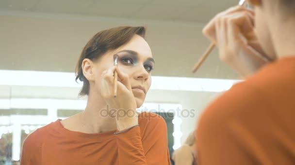 junges schönes Mädchen zieht Schatten auf die Augenlider. Sie steht vor dem Spiegel und schminkt sich.