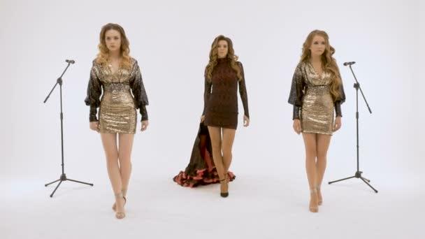 Tři sexy holky se pomalu pohybují v ateliéru, proti bílé zdi. Skvělé zázemí pro vaše video.
