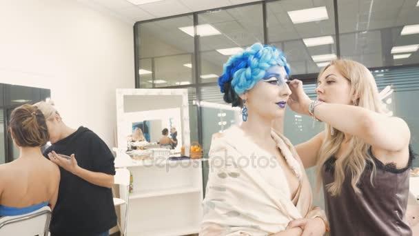 Zwei Maskenbildner schminken Models. Vorbereitung auf ein künstlerisches Fotoshooting