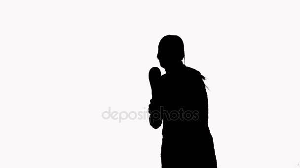Silueta dívky, která tančí s maracas. Na bílém pozadí