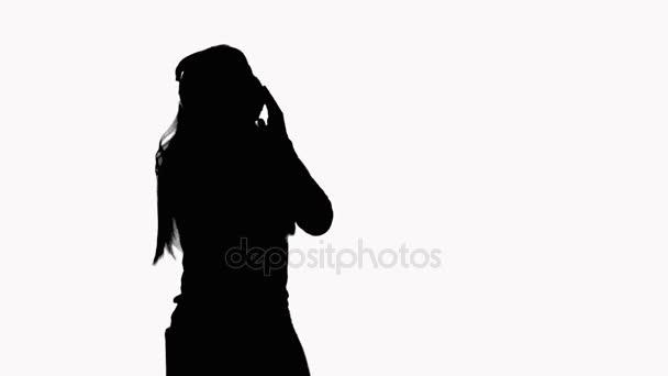 Silueta dívky s dlouhými vlasy, která poslouchá hudbu přes sluchátka. Ta se pohybuje krásně. Na bílém pozadí. Nahrávání videoklip.