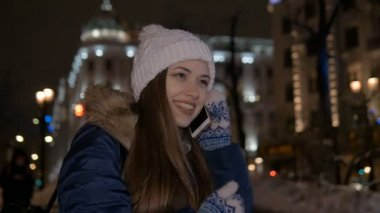 Slow motion. Beautiful girl smiles and talks on the phone. In the street in winter, in the evening.