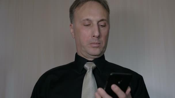 Podnikatel používá chytrý telefon do práce.