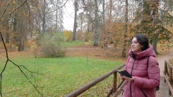 Herbst Park Kaukasische Frau mittleren Alters schießt die Natur auf dem Smartphone, was sagt