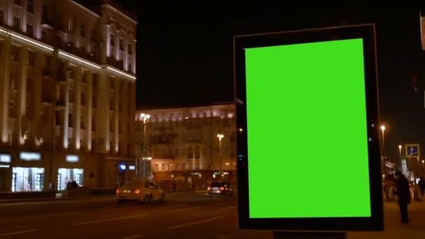 Showcase nagy zöld képernyővel. Jönnek az autók. Városi utca. Jó estét..