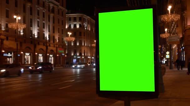 Városi utca. - Jó estét! Showcase nagy zöld képernyővel. Jönnek az autók..