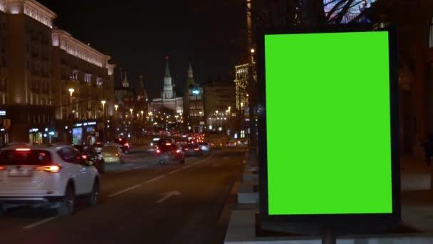 Přehlídka s velkou zelenou obrazovkou. Přijíždějí auta. City Street. Večer.