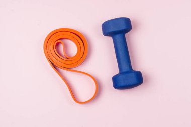 Orange Band for Fitness or Exercise and Blue Dumbbell on Pink Background Top View Flat Lay Horizontal Weight Loss Concept