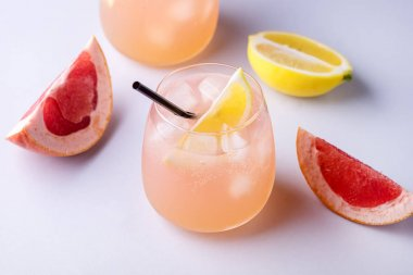 Two Glasses of Cocktail with Grapefruit and Lemon Citrus Drink or Lemonade with Ice Cubes and Straw Blue Background