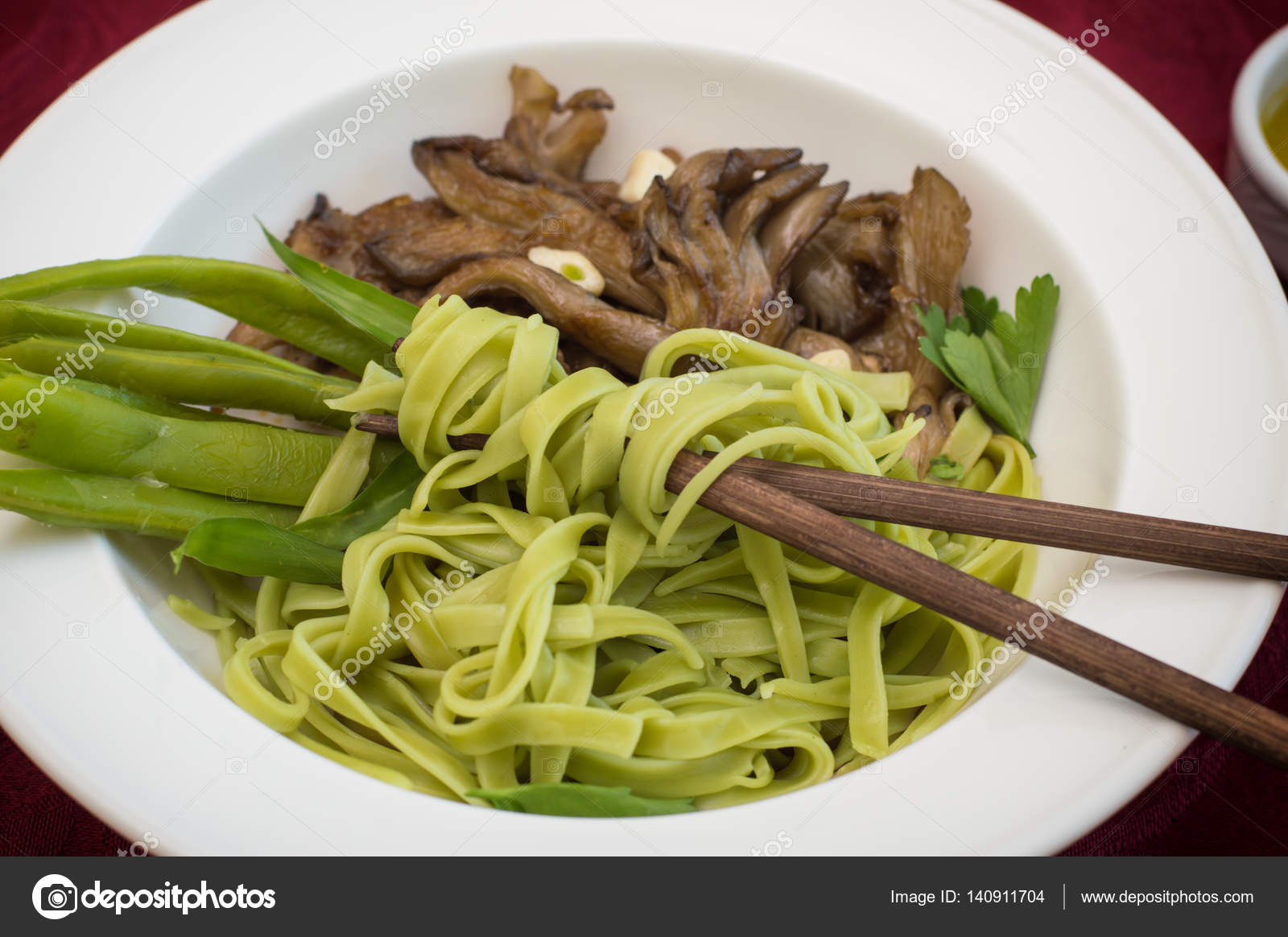 Teller mit Spaghetti-Teig mit Spinat und Austernpilze. Italienische ...
