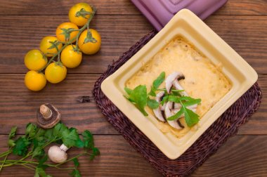 Hot Julienne with juicy chicken, mushrooms, cream sauce and cheese. Meat appetizer. Wooden background. Top view. Close-up