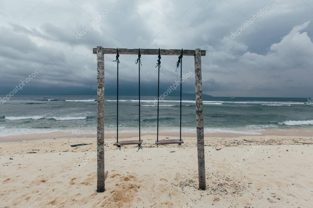 wooden swings on seashore