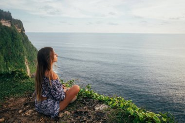 Beautiful girl relaxing on cliff
