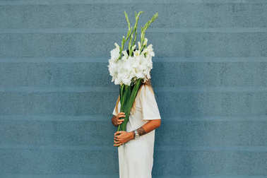 Woman hiding face with flowers