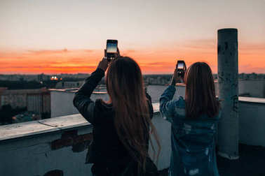 Women taking photos of sunset