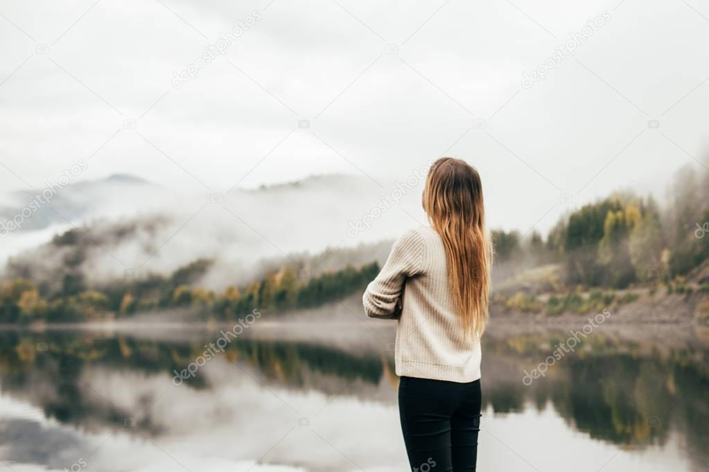 Girl looks on the foggy lake in Norway