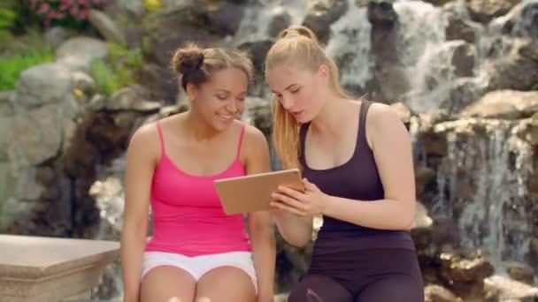 Sledujete na tabletu venkovní foto mladé ženy. Přátelé pomocí tabletového počítače