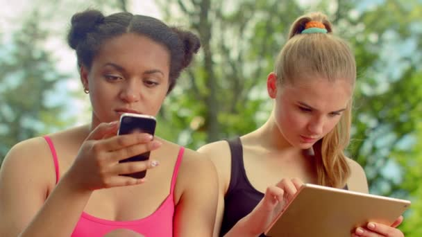 Girls using smartphone and ipad in park. Friends surfing internet on tablet