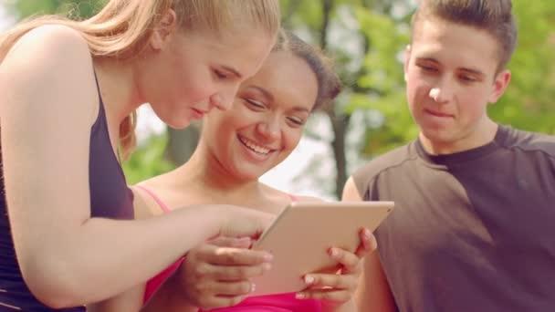 Mladí přátelé surfování internetu na tabletu. Zblízka šťastných lidí baví
