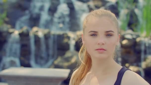 Blond žena pózuje v parku. Portrét mladé ženy poblíž vodopád
