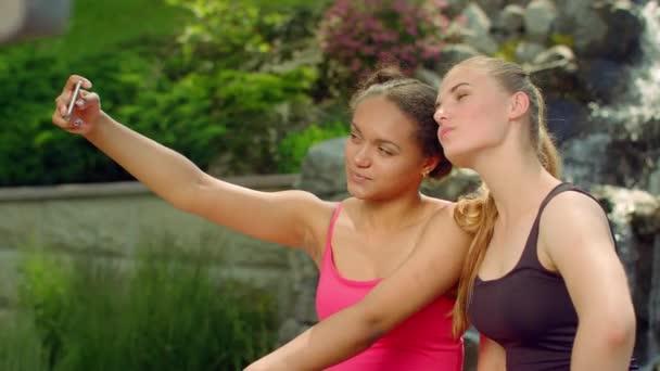 Selfie friends outdoors. Joyful girls having fun in park taking selfie