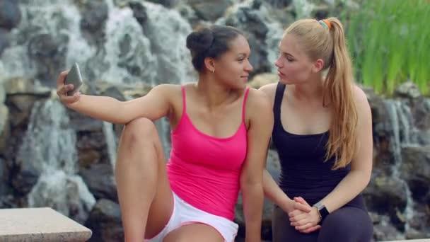 Female friends taking selfie near waterfall. Multiracial girls taking photo