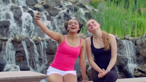 Young women taking selfie near waterfall. Multiracial women taking seflie