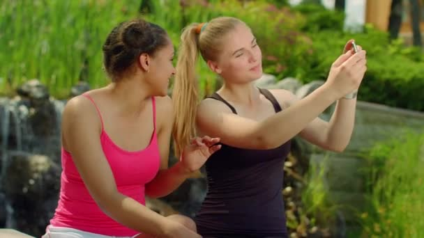 Happy girlfriends taking photo with smartphone in park. Selfie friends outdoors