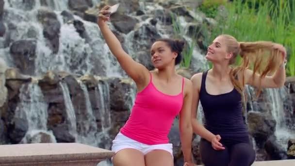 Selfie women. Two young women taking selfie near waterfall. Women selfie