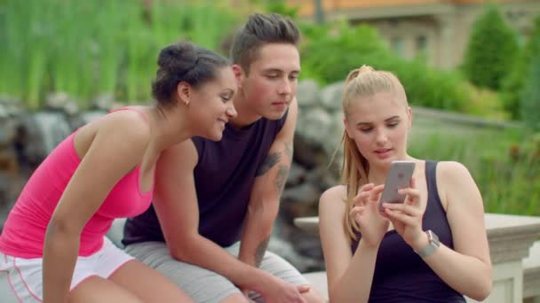 Cheerful friends watching photos on smartphone