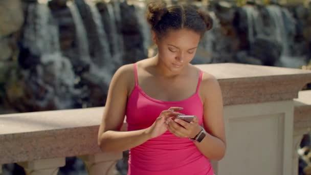 Latin Girl mit Smartphone im Park. Afrikanerin mit Telefon im freien