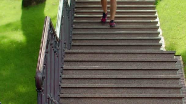 Muž běží dolů po schodech. Fitness muž běží dole v parku