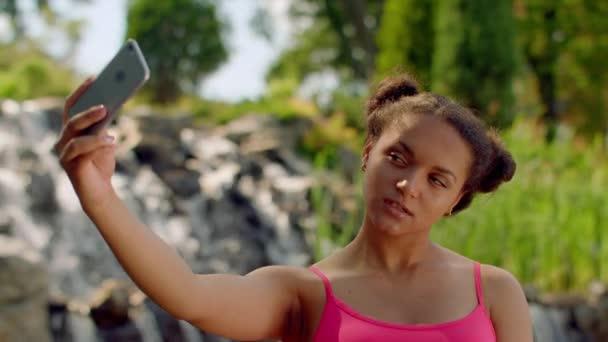 Girl taking selfie photo. Selfie girl showing v sign. African girl taking selfie