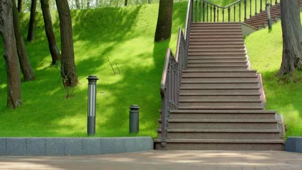 Žulové schody v parku. Schodiště v zeleném parku. Kamenné schody v městském parku