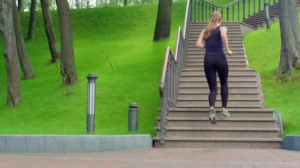 Žena, běh do schodů v pomalém pohybu. Skutečné ženy vyběhnout do schodů v parku