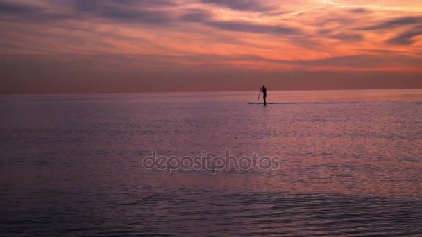 Západ slunce na moři. Muž na surfu při západu slunce. Západ slunce na moři. Západ slunce na šířku