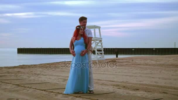 Schwangere paar am Strand bei Sonnenaufgang. Liebespaar am Strand Meer umarmt