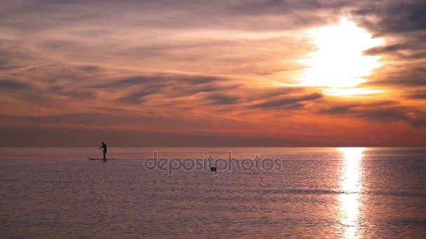 Sagoma di uomo a bordo di surf in mare al tramonto. Tramonto sul mare. Riflessione del sole